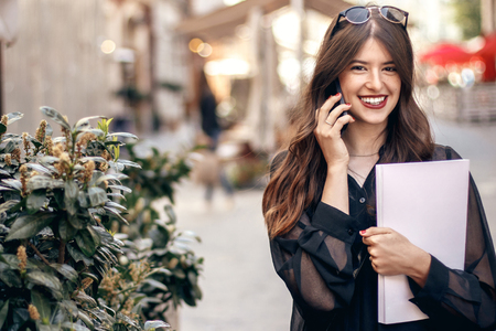 beautiful stylish woman walking in sunny city street, holding phone and magazine. happy hipster girl dressed in fashionable outfit, talking on smartphone in european city. copy space Stockfoto