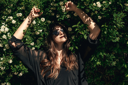 beautiful Stylish Hipster Girl with beautiful hair relaxing at floral bushes in sunny day. Gorgeous Boho Woman with sunglasses in fashionable outfit enjoying day in flowers in garden
