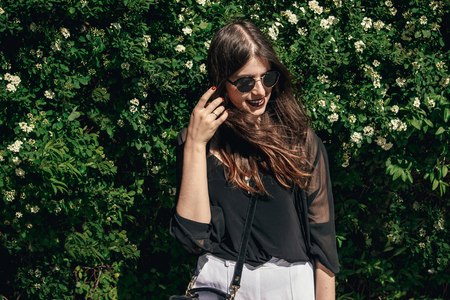 beautiful Stylish Hipster Girl with beautiful windy hair having fun at floral bushes in sunny day. Boho Woman with sunglasses in fashionable outfit, smiling and enjoying day in garden