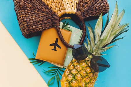 summer vacation flat lay. stylish bag,hat,passport with map and pineapple in sunglasses on blue and yellow trendy paper background. travel and wanderlust concept