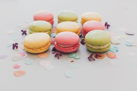 tasty pink, yellow, green  macaroons on trendy pastel gray paper with lilac flowers and confetti. space for text. delicious colorful macaroons candy for party. yummy background