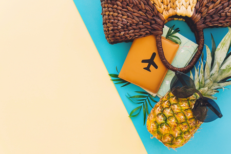 stylish bag,hat,passport with map and pineapple in sunglasses, on blue and yellow trendy paper background flat lay,space for text. travel and wanderlust concept. summer vacation