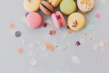 delicious colorful macaroons on trendy pastel gray paper with lilac flowers and confetti, flat lay. tasty pink, yellow, green and brown macaroons. space for text. candy for party