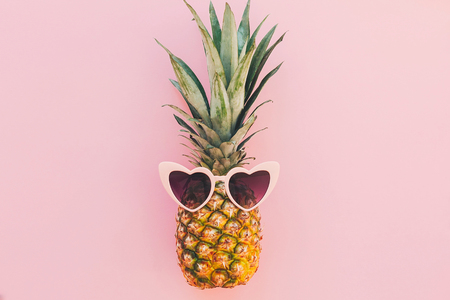 stylish pineapple in pink sunglasses on trendy pink paper background. flat lay. summer vacation and party concept. space for text. hipster summer travel and holidays