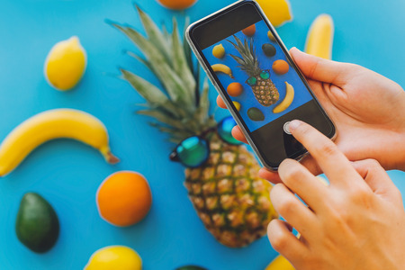 hands holding phone and taking photo of stylish pineapple in sunglasses and bananas, oranges, lemons, avocado on blue trendy paper, flat lay.