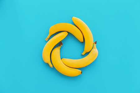 yellow bananas in circle on blue paper  trendy background, flat lay. bright summer flat lay concept. juicy abstract background, pop art style. modern image, fruits top view