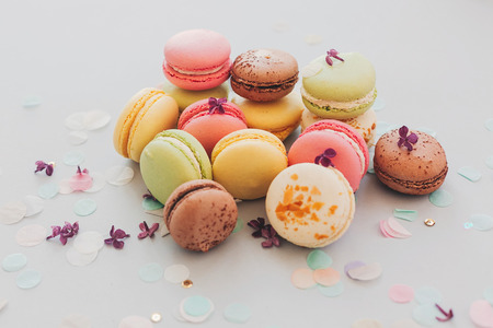 tasty pink, yellow, green and brown macaroons on trendy pastel gray paper with lilac flowers and confetti. space for text. delicious colorful macaroons candy for party. yummy background