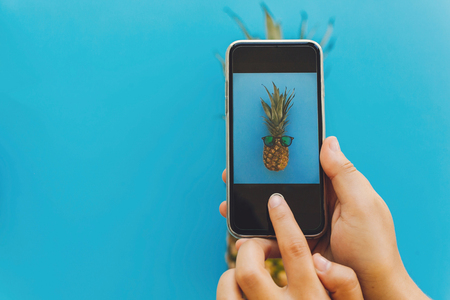 blogging workshop concept. hands holding phone and taking photo of pineapple in stylish sunglasses on blue trendy paper background, flat lay. space for text. Stockfoto