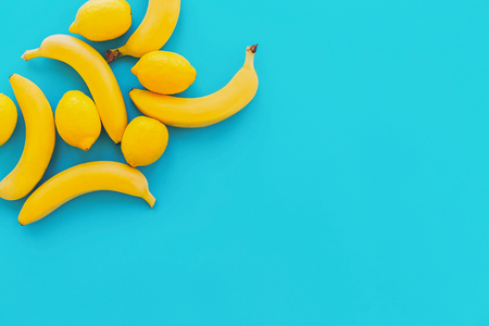 yellow bananas with lemons on blue paper trendy background, flat lay. bright summer flat lay concept, with space for text. juicy abstract background, pop art style. modern image Stock Photo