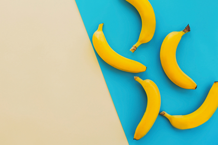 summer flat lay. yellow bananas on blue paper trendy background, flat lay. bright colorful photo, with space for text. juicy abstract background, pop art style. modern image Stockfoto