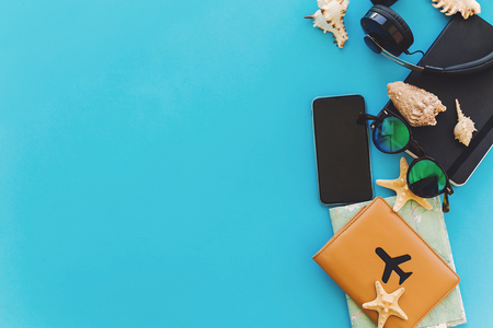 stylish black phone, passport, sunglasses, map, headphones, shells, notebook on bright trendy blue paper background, flat lay. space for text. summer vacation. travel and wanderlust concept