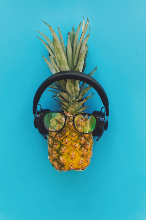 pineapple in stylish hipster glasses and black headphones on blue trendy paper background, flat lay. modern summer vacation concept. fruit flat lay, pool party theme