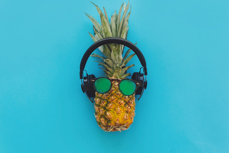 pineapple in stylish hipster sunglasses and black headphones on blue trendy paper background, flat lay. modern summer vacation concept. fruit flat lay, pool party and music theme Stock Photo