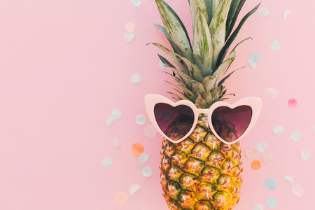 summer vacation and party concept. flat lay. stylish pineapple in pink sunglasses on trendy pink paper background with confetti. space for text. summer travel and holidays Stock Photo
