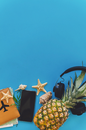 summer vacation and travel flat lay. stylish black phone, passport, sunglasses, map, pineapple with headphones, shells on trendy blue paper. space for text.  wanderlust. vertical photo