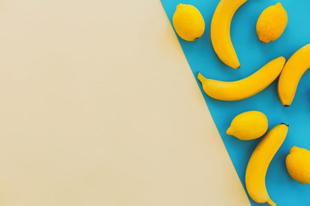 summer flat lay. yellow bananas with lemons on blue paper trendy background, flat lay. bright colorful photo, with space for text. juicy abstract background, pop art style. modern image