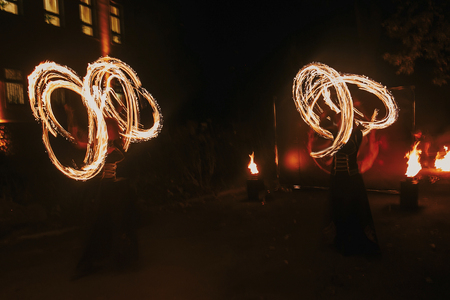 amazing fire show at night at festival or wedding party. Fire dancers swing, spinning fire and man juggling with bright sparks in the night. fire show performance and entertainment