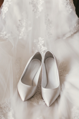 beautiful stylish shoes on luxury silk wedding dress. simple white shoes on white gown with lace floral ornaments, bridal morning preparations