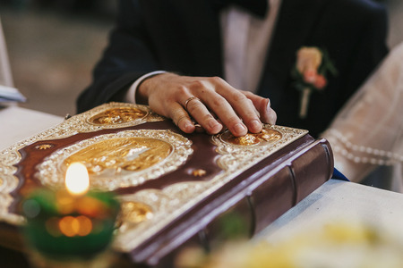 bride and groom holding hands on golden bible on holy altar during wedding ceremony in church, exchanging oaths. spiritual moments of holy matrimony Stock Photo