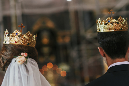 bride and groom standing with golden crowns with cross at holy altar during wedding ceremony in church, back view. spiritual moments of holy matrimony