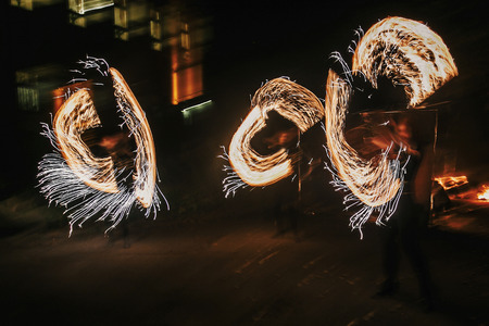 Fire dancers swing, spinning fire and man juggling with bright sparks in the night. fire show performance and entertainment. amazing fire show at night at festival or wedding party. 스톡 콘텐츠