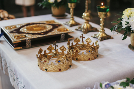 golden crowns and bible on holy altar during wedding ceremony in church. spiritual moments of holy matrimony
