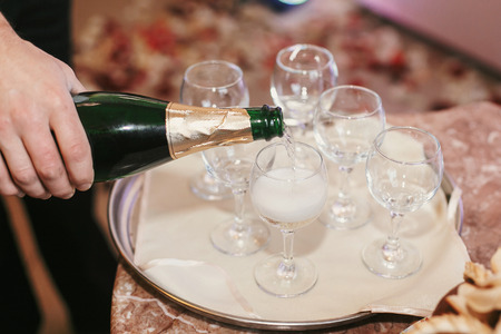 waiter pouring champagne into empty glases at wedding reception. holiday celebrations. luxury catering in restaurant