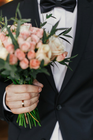 groom holding stylish bouquet with roses and eucalyptus. morning preparations before wedding day. groom waiting for his bride