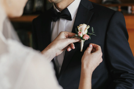 beautiful bride putting on stylish simple boutonniere with roses on groom black suit. wedding morning preparations Standard-Bild