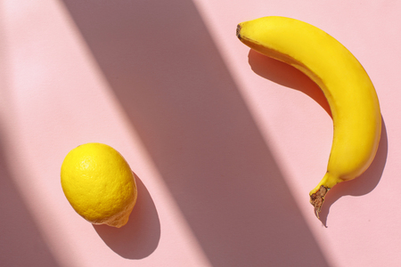 juicy lemon and banana on trendy pink paper background in sun light. flat lay. creative contrast summer image. vacation and diet concept. space for text. tropical summer holidays 版權商用圖片