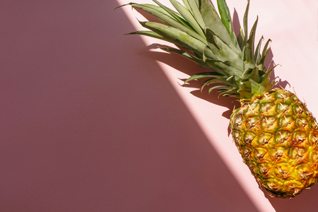 juicy pineapple on trendy pink paper background in sun light. flat lay. creative contrast summer image. vacation and party concept. space for text. tropical summer holidays 版權商用圖片