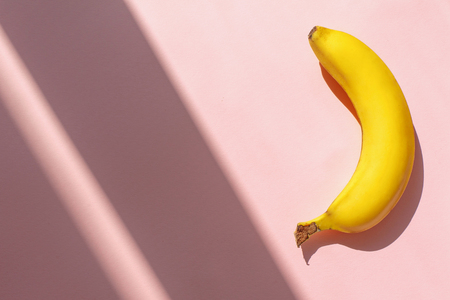juicy banana on trendy pink paper background in sun light. flat lay. creative contrast summer image. vacation and diet concept. space for text. tropical summer holidays