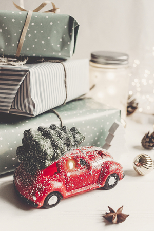 modern christmas ornaments and car toy with tree, presents cones anise on white wooden background. merry christmas concept. seasonal greetings. happy holidays, xmas card, hygge Stock Photo