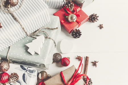 christmas flat lay. wrapped presents with ornaments  and pine cones anise and lights on rustic white wooden background top view. stylish gifts. seasonal greetings. happy holidays