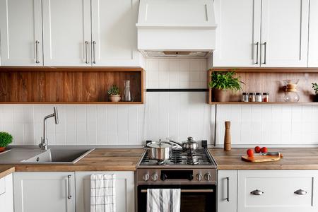 Stilvolles Kücheninterieur mit modernen Schränken und Edelstahlgeräten in neuem Zuhause. Design im skandinavischen Stil. Essen zubereiten. Grünpflanzen Dekor, Holzarbeitsplatte, Spüle und Herd Standard-Bild