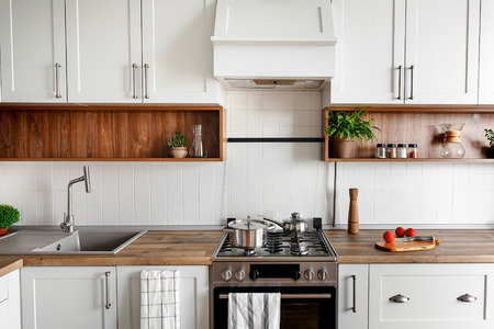 Stylish kitchen interior with modern cabinets and stainless steel appliances in new home. design in scandinavian style. cooking food. green plants decor, wooden worktop, sink and stove Archivio Fotografico