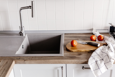 wooden board with knife, tomatoes, towel, spices on modern kitchen countertop  near granite sink and steel faucet. cooking food. Stylish gray kitchen interior Zdjęcie Seryjne
