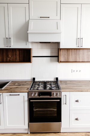 Stylish light gray kitchen interior with modern cabinets and stainless steel appliances in a luxury new house. kitchen design in scandinavian style. hardwood floor and wooden countertop
