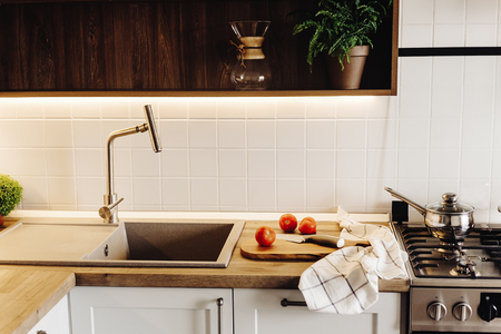 wooden board with knife, tomatoes on modern kitchen countertop near granite sink and steel faucet. cooking food. Stylish kitchen interior design in scandinavian style, steel appliances