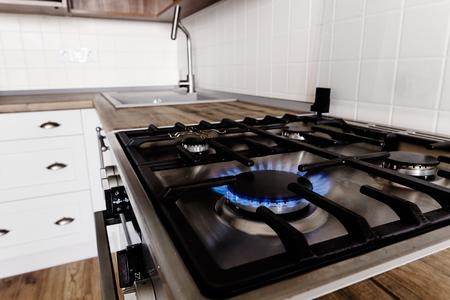 gaz bleu brûlant d'une cuisinière élégante. Close-up flammes sur cuisinière moderne dans un élégant intérieur de cuisine gris clair avec des meubles modernes et des appareils en acier inoxydable dans une nouvelle maison Banque d'images
