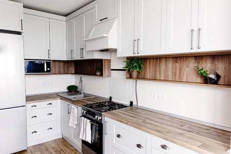 Kitchen design in modern scandinavian style. stylish light grey kitchen interior with modern furniture and stainless steel appliances in a new house. wooden countertop, steel stove,sink and faucet Stock fotó