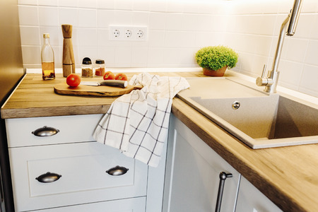 wooden board with knife, tomatoes, olive oil, spices, pepper mill on modern kitchen countertop and near granite sink and steel faucet. cooking food. Stylish gray kitchen interior