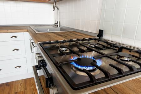 brennendes Gas vom Küchenherd auf Hintergrund des stilvollen Kücheninnenraums mit modernen Schränken und Edelstahlgeräten. Flammen vom modernen Herd. Design im skandinavischen Stil Standard-Bild