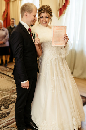 happy gorgeous bride and stylish groom holding official document wedding register, emotional moment, ceremony Stock Photo - 104926522