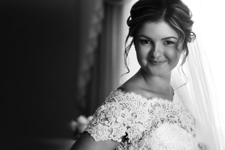 luxury gorgeous blonde bride getting dressed in the morning with helping bridesmaids in bright room Фото со стока