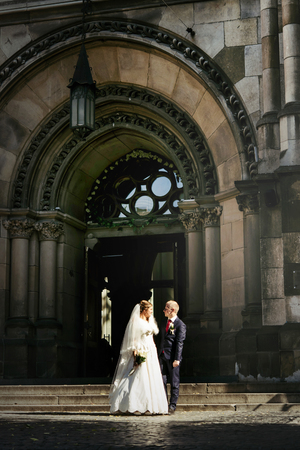 happy gorgeous bride and stylish handsome groom  on background of an amazing building church in the city