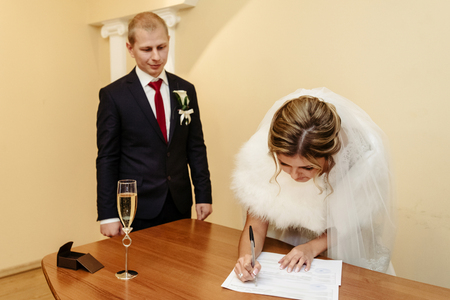 happy gorgeous bride and stylish groom signing official document wedding register, emotional moment, ceremony Stock Photo