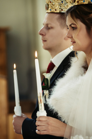 wedding ceremony of happy elegant blonde bride and stylish groom, holding candles in the old church Stock Photo