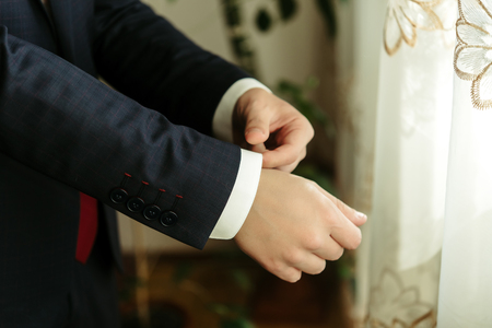 happy gorgeous handsome groom getting ready dressed in the morning on background of a room Stock fotó