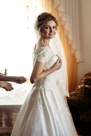 luxury gorgeous blonde bride getting dressed in the morning with helping bridesmaids in bright room Фото со стока - 104926673